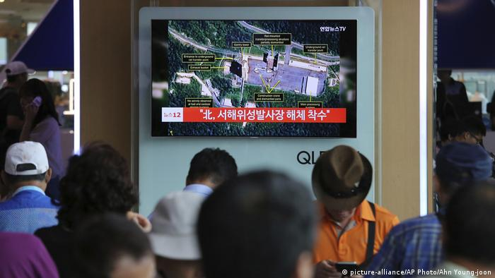 A TV screen shows a satellite image of North Korea's Sohae launch site