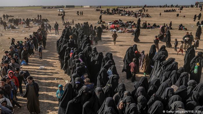 Civilians evacuated from the 'Islamic State' group's holdout of Baghouz wait at a screening area held by the Syrian Democratic Forces (Getty Images/AFP/B. Kilic)
