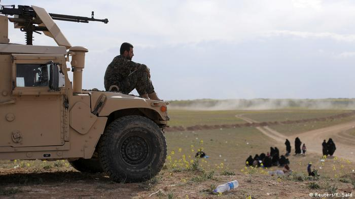 An SDF fighter looks on as civilians flee Baghouz