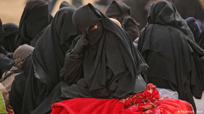 A fully veiled IS woman sits on a blanket near Baghouz (Reuters/R. Said)