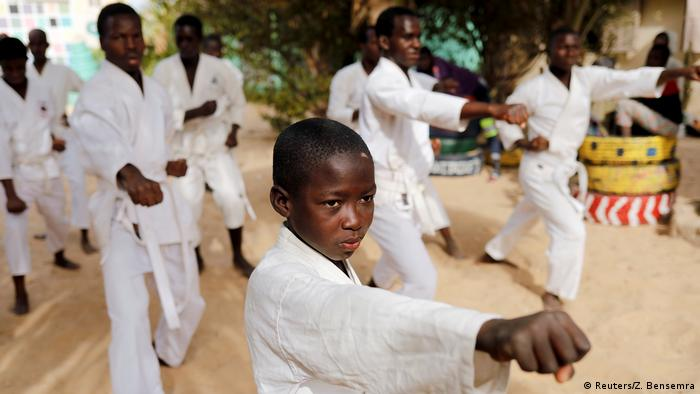 Boys and young men in traditional karate garb go throughthe moves
