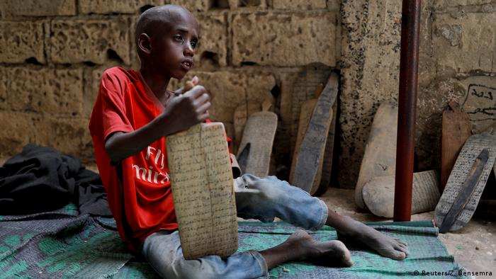 A young boy sits on the floor of a daara and holds a wooden board on which Koran verses have been scribed