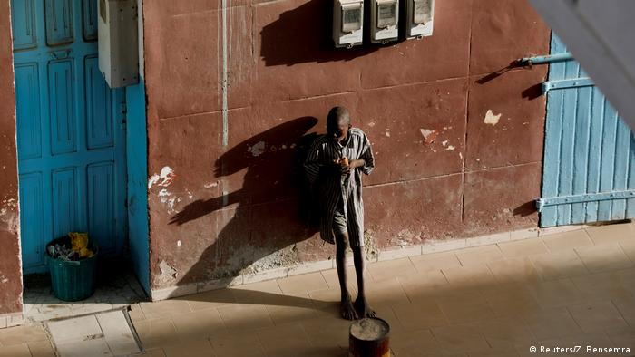 A young boy leans against a wall in the Senegalese city of Saint Louis and eats while he begs.