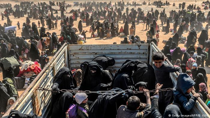 Women and children sit in the back of a truck and many more stand around it as evacuations from the last IS stronghold in Syria take place (Getty Images/AFP/B. Kilic)