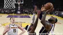 Los Angeles Lakers forward LeBron James, right, shoots and scores as Denver Nuggets forward Torrey Craig, center, defends and center Nikola Jokic watches during the first half of an NBA basketball game Wednesday, March 6, 2019, in Los Angeles. With the basket, James moved past Michael Jordan for fourth place on the NBA career scoring list. (AP Photo/Mark J. Terrill)  