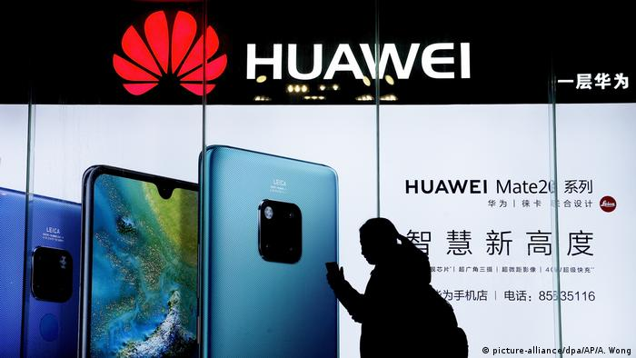 A woman walks past a Huawei store
