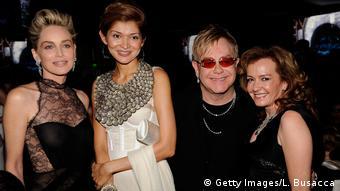 A filha do ex-ditador do Uzbequistão Gulnara (centro), entre Sharon Stone e Elton John