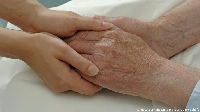 A young and old woman holding hands