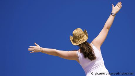 Young woman stretches arms to blue sky
