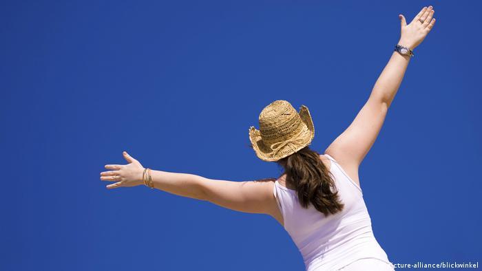 Junge Frau streckt Arme zum blauen Himmel