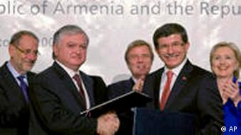 Armenian foreign minister Edouard Nalbandian and Turkish foreign minister Ahmet Davutoglu shake hands while European Union foreign affairs chief Javier Solana, French foreign minister Bernard Kouchner, and US Secretary of State Hillary Rodham Clinton applaude during the signing ceremony between Armenia and Turkey in Zurich in 2009