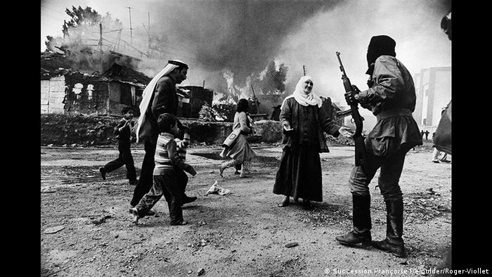 A woman holds out her hands at a gunman as children run by and buildings burn in the background (Succession Françoise Demulder/Roger-Viollet)