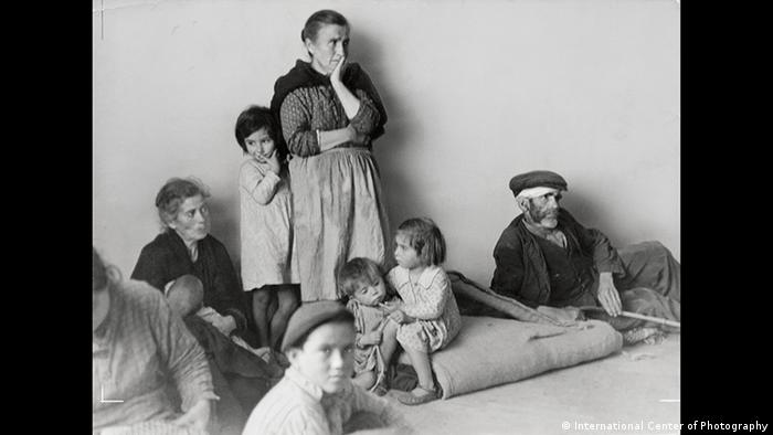 A woman looks worried as children sit around her (International Center of Photography)