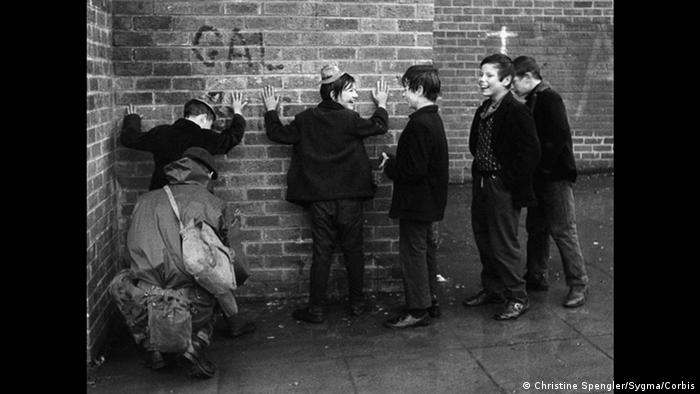 Boys hold their hands up against a brick wall as they laugh together (Christine Spengler/Sygma/Corbis)