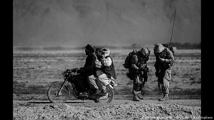 Men in baggy clothes ride a motor bike past two heavily equipped soldiers (picture-alliance/AP Images/Anja Niedringhaus)