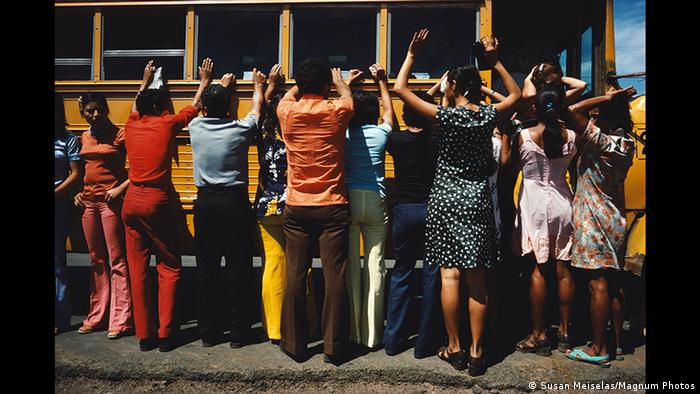 Men and women hold up their hands to be searched against a yellow bus (Susan Meiselas/Magnum Photos)