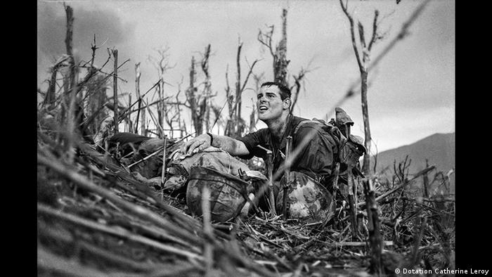 A soldier looks up as he puts his arm around a dead comrade lying in a bramble of dead trees (Dotation Catherine Leroy)