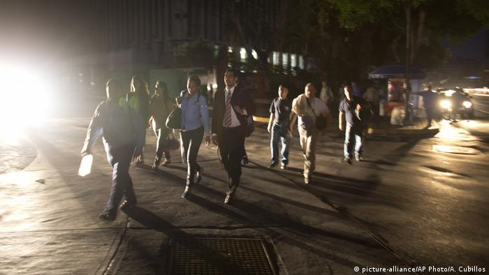 Venezuelans walk home after work during a power outage