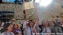 08.03.2019 +++ A member of the liberal Jewish religious movement Women of the Wall (WOW), wearing phylacteries and Tallit traditional Jewish prayer shawls for men, holds up a Torah scroll during an event marking the organisation's 30th anniversary and the start of the Jewish month (Rosh Hodesh) of Adar Bet, at the egalitarian prayer section (also known as Ezrat Israel) on the southern side of Judaism's holiest prayer site of the Western Wall in the Old City of Jerusalem on March 8, 2019. (Photo by GALI TIBBON / AFP) (Photo credit should read GALI TIBBON/AFP/Getty Images)