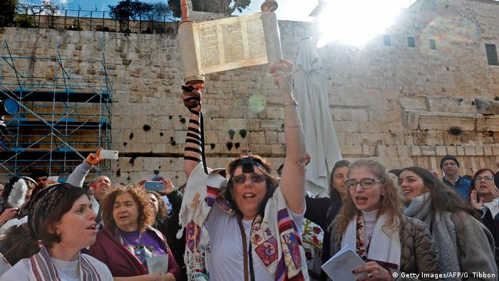 A member of the Women of the Wall holds up a Torah scroll at an event at the Western Wall in Jerusalem