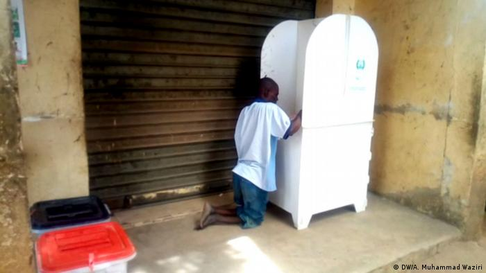 A disabled man kneels as he casts his vote in a white ballot box in Nigeria