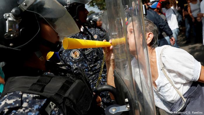 BdTD Venezuela Caracas Frau bläst Polizisten den Marsch