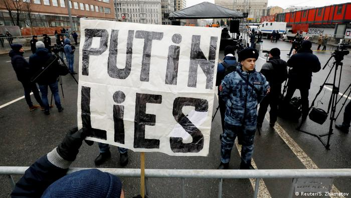 A protest against Putin in Russia where someone holds a sign with Putin lies on it