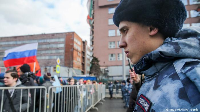 Russian serviceman watches crowd of protesters in Moscow