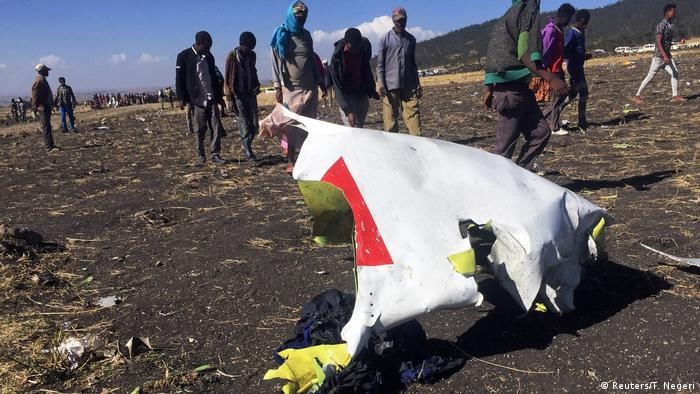 People walk past a part of the wreckage at the scene of the Ethiopian Airlines Flight ET 302