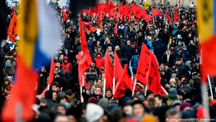 People attend an opposition rally in central Moscow carrying flags and banners to demand internet freedom in Russia