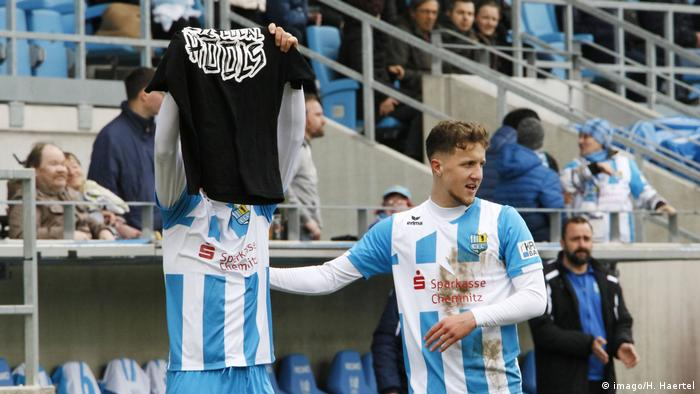 Daniel Frahn holds up a shirt with a pro-hooligan message (imago/H. Haertel)