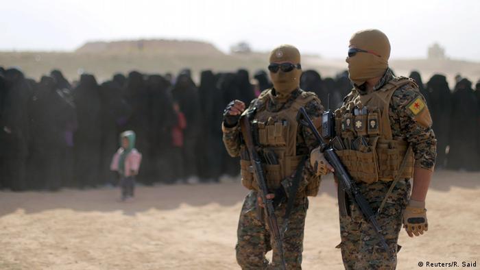 SDF fighters patrol displaced women near Baghouz