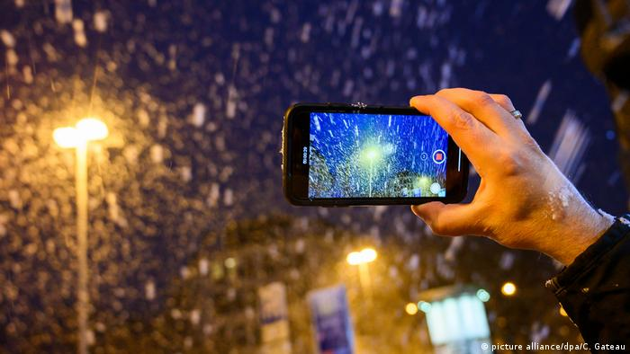 A man films snow falling in Hanover, Germany (picture alliance/dpa/C. Gateau)