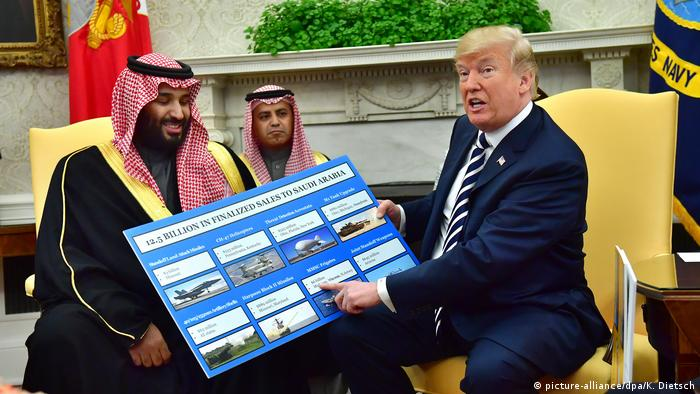 US President Donald Trump points to a picture of the weapons systems the US has just sold to Saudi Crown Prince Mohammed bin Salman, sitting next to him.