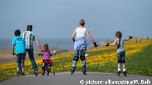 ARCHIV - 22.04.2011, Niedersachsen, Campen: Ein Mann, eine Frau und drei Kinder fahren mit Inline-Skates, einem Fahrrad und einem Roller den Deich hinunter. (Zu dpa «Schlaue Eltern haben fittere Kinder») Foto: Matthias Balk/dpa +++ dpa-Bildfunk +++ | Verwendung weltweit