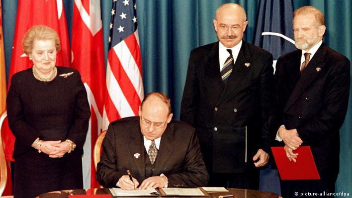 Глава МИД Чехии подписывает документ о вступлении страны в НАТО. Слева от него - госсекретарь США Олбрайт, справа - коллеги из Венгрии и Польши