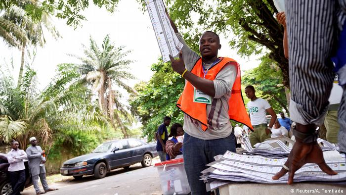 A man holds up a ballot paper during the counting process