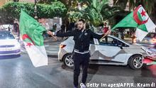 An Algerian youth waves national flags during a demonstration in the centre of the capital Algiers on March 11, 2019, after President Abdelaziz Bouteflika announced his withdrawal from a bid to win another term in office and postponed an April 18 election, following weeks of protests against his candidacy. - Bouteflika, in a message carried by national news agency APS, said the presidential poll would follow a national conference on political and constitutional reform to be drawn up by the end of 2019. (Photo by RYAD KRAMDI / AFP) (Photo credit should read RYAD KRAMDI/AFP/Getty Images)