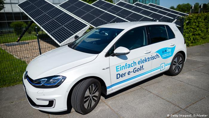 Electric car in front of solar panels at a Volkswagen factory in Dresden, Germany