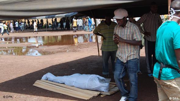 Eine verhüllte Leiche liegt am Boden des Stadions von Conakry am 28. September 2009 (Foto: dpa)