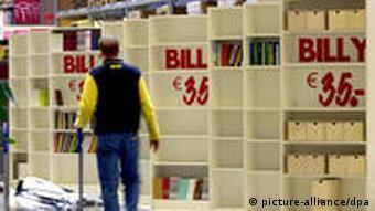 Ein Ikea-Mitarbeiter schiebt in einer Filiale einen Einkaufswagen an dem Allround-Regal Billy vorbei (Foto: dpa)