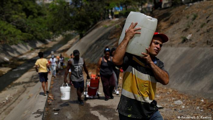 Жители Венесуэлы несут в канистрах воду из реки Гуайре вблизи Каракаса