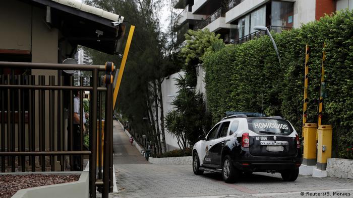 Carro da polícia civil atravessa a portaria do Condomínio Vivendas da Barra, no Rio de Janeiro