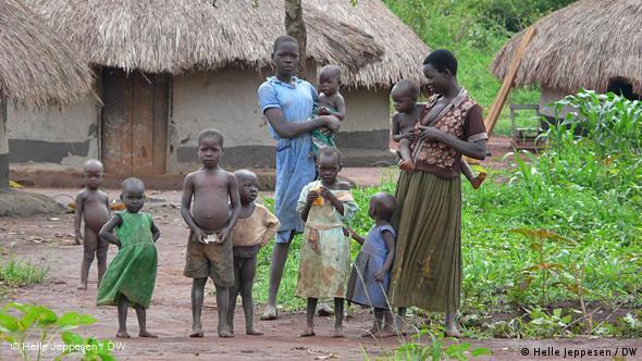 Ugandische Familie vor ihrer Hütte