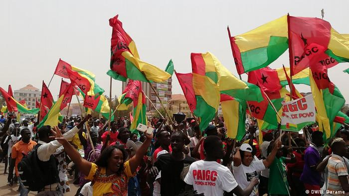 Supporters of the PAIGC party in Guinea-Bissau wave red, green and yellow flags as they celebrate the party's victory in the 2019 parliamentary election