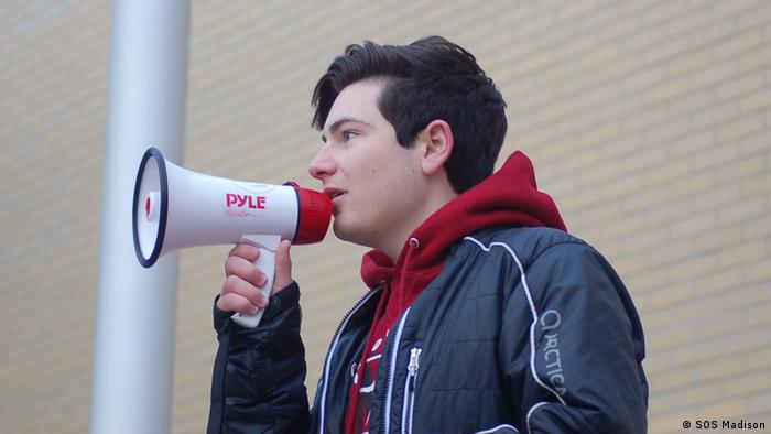 Male climate activist speaks into megaphone in Wisconsin, USA