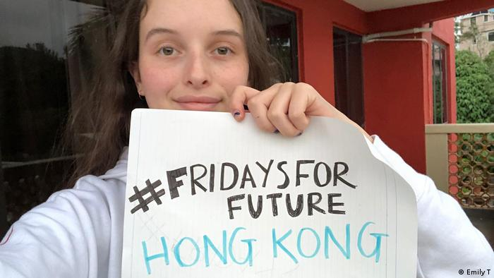 Female climate striker with banner (#FRIDAYSFORFUTURE HONG KONG) in Hong Kong