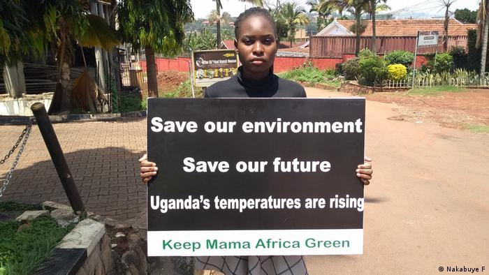 Female climate strike activist with banner (Save our environment / Save our future / Uganda's temperatures are rising / Keep Mama Africa Green) in Uganda, Africa
