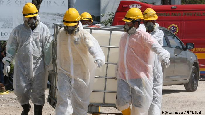 Emergency personnel wearing protective suits prepare materials for the cleanup of the Sungai Kim Kim River in Pasir Gudang, southern Malaysia, on March 14, 2019