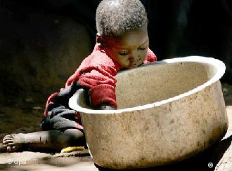 African Boy with empty metal cooking pot